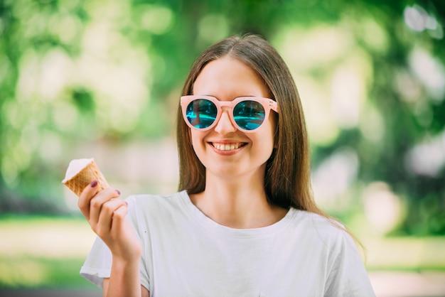 Verrücktes mädchen des jungen hippies des porträts im freien, das runde spiegelsonnenbrille des eiscremesommerwetters isst