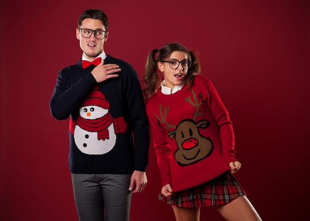 Verrücktes nerd-paar in lustigen pullovern, die herumalbern