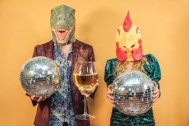 Verrücktes paar, das spaß beim feiern der silvesterparty mit discokugeln und einem glas wein hat - konzentrieren sie sich auf t-rex und hühnermaske