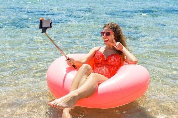 Verrücktes schwimmen mit aufblasbarem donut macht selfie am strand am sonnigen tag des sommers
