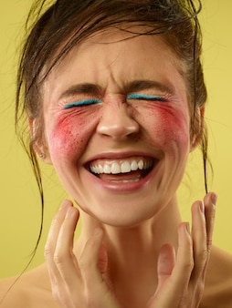 Verrücktester spaß. schönes weibliches gesicht mit perfekter haut und hellem make-up. konzept der natürlichen schönheit, hautpflege, behandlung, gesundheit, spa, kosmetik. ein kreativer künstlerischer bühnenakt und charakteristischer charakter.