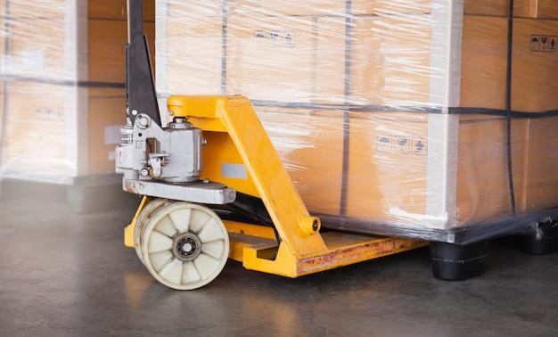 Versand, frachtexport und versandlager. nahaufnahme handpalettenwagen oder palettenheber handlift mit palettenware.