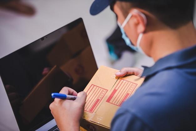 Versand online-shopping kleinunternehmer schreiben auf kartons bei der arbeit für kleine kmu-unternehmer auswirkungen der krise covid-19 online-verkaufsgeschäft