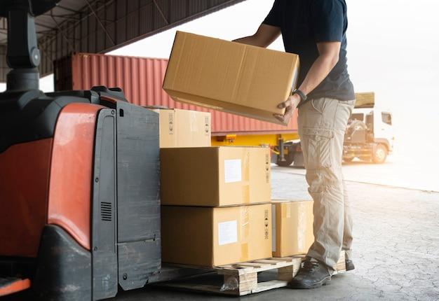 Versandkartons. lagerarbeiter, der pappkartons hebt, die auf palette stapeln.
