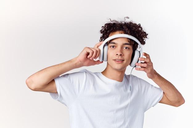 Versauter kerl mit kabelgebundenen kopfhörern, die musik-teenagermodell der neuen technologie hören
