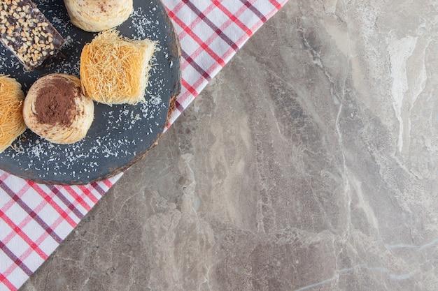 Verschieden desserts auf einem brett auf geschirrtuch auf marmor.