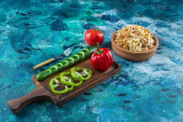 Verschieden gemüse auf einem brett neben einer gabel und einer schüssel nudel auf dem blauen tisch.
