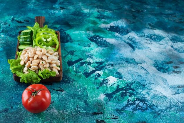 Verschieden gemüse und bohnen auf einem brett auf dem blauen tisch.