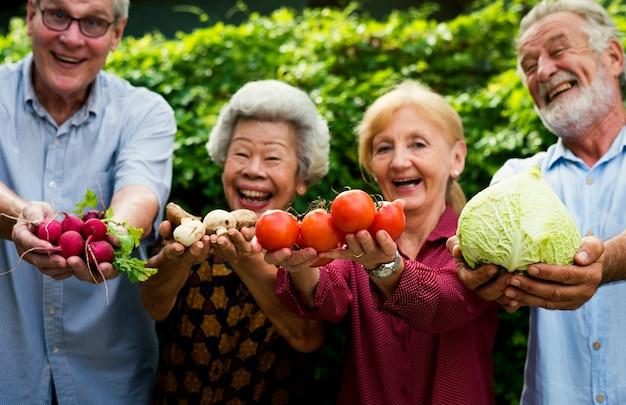 Verschiedene ältere leute, die gemüse in ihren händen halten