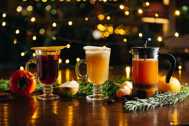 Verschiedene alkoholische heiße cocktails im herbst oder winter. mandarinentee in französischer presse, glühbirnenmost und glühwein mit persimone