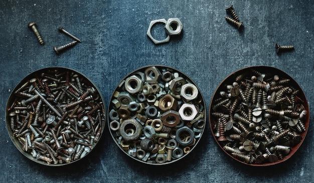 Verschiedene alte muttern und schrauben in runden blechdosen, nahaufnahme