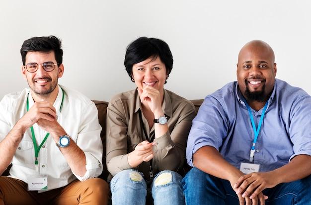 Verschiedene arbeitskräfte, die zusammen auf couch sitzen