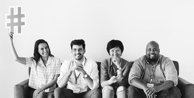 Verschiedene arbeitskräfte, die zusammen die frau hält hashtagikone sitzen