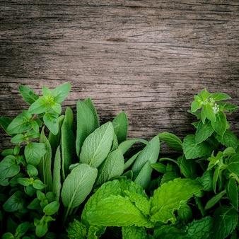 Verschiedene aromatische kräuter und gewürze gründen auf altem hölzernem hintergrund.