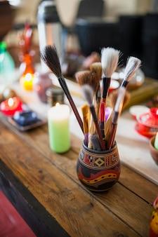 Verschiedene art von chinesischen pinseln in der halterung über dem holztisch mit brennenden kerzen
