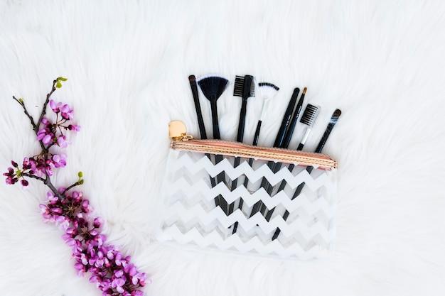 Verschiedene art von make-upbürsten in der transparenten plastiktasche mit dem purpurroten blumenzweig auf weißem pelz