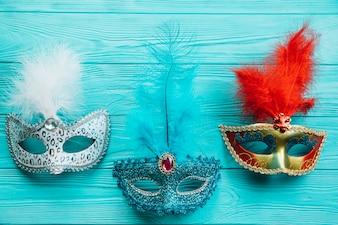 Verschiedene Arten der Maskeradekarnevalsmaske mit Feder auf blauem Holztisch