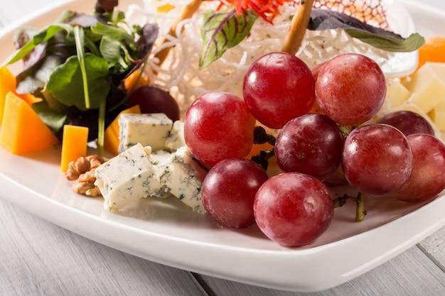 Verschiedene arten der restaurantkäseplatte mit trauben und walnuss auf weißer platte.