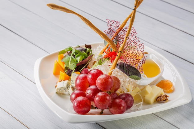 Verschiedene arten der restaurantkäseplatte mit trauben, walnuss und soße auf weißer platte