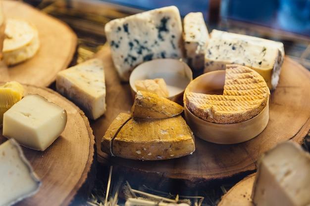 Verschiedene arten des käses auf rustikalem hölzernem hackendem brett.