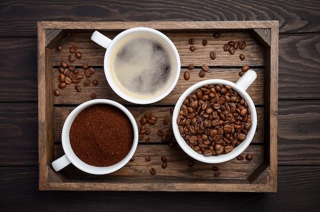 Verschiedene arten des kaffees - boden, korn und getränk auf dunkler draufsicht des holztischs