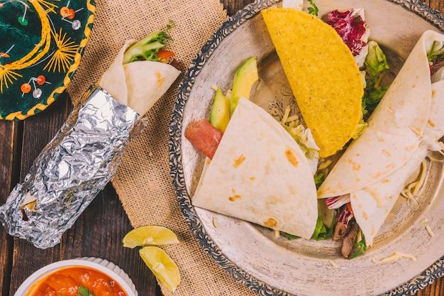 Verschiedene arten des köstlichen mexikanischen lebensmittels in der platte mit hut