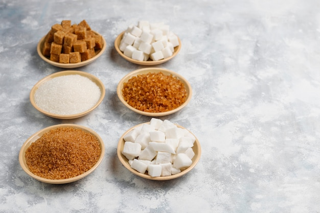 Verschiedene arten des zuckers, des braunen zuckers und des weiß auf konkreter, draufsicht