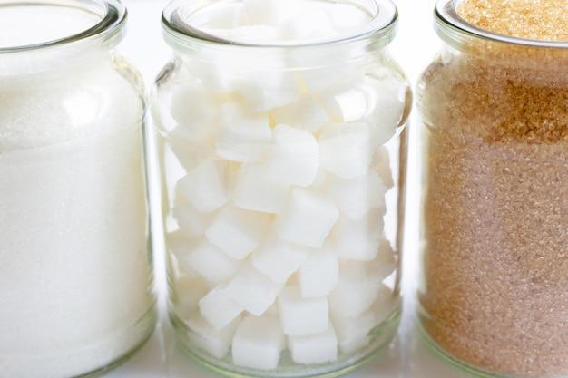 Verschiedene arten des zuckers in einem glasgefäß auf weiß
