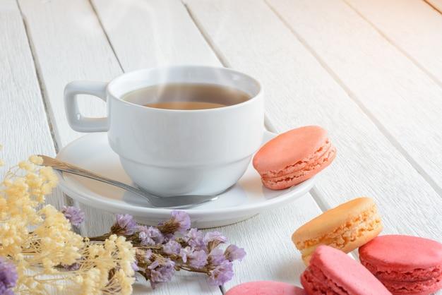 Verschiedene arten farbe von makronen mit schale heißem tee auf weißer holzoberfläche