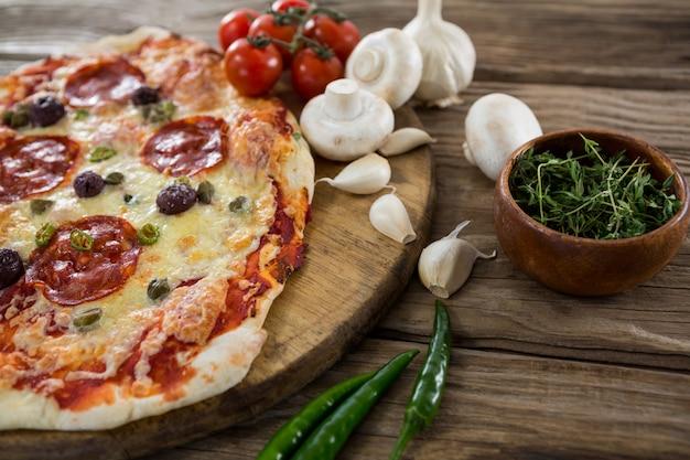Verschiedene arten mit pizza und tomate auf einem holztablett