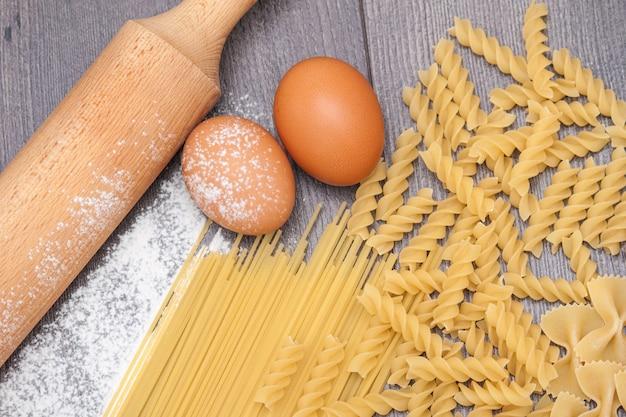 Verschiedene arten oder rohe teigwaren auf dem hölzernen hintergrund und bestandteile für teigwareneier, mehl.