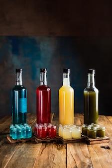 Verschiedene arten von alkoholischen schützen oder schüsse mit flaschen, rot, grün, gelb, blau