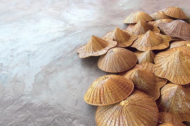 Verschiedene arten von asiatischen konischen hüten auf den souvenirmärkten der touristen in thailand