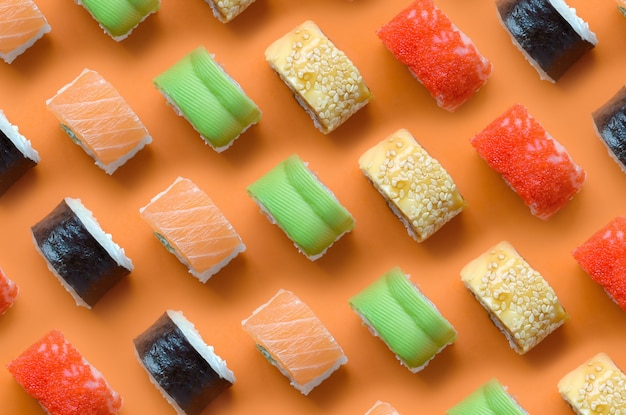Verschiedene arten von asiatischen sushi-rollen auf orange hintergrund. flaches lay-muster der minimalismus-draufsicht mit japanischem essen