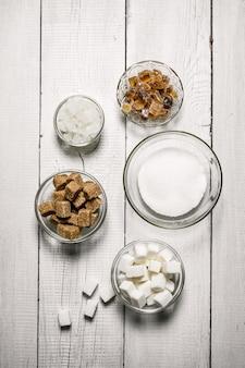 Verschiedene arten von braunem und weißem zucker in tassen auf weißem holztisch.