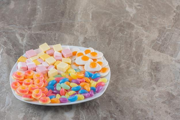 Verschiedene arten von bunten bonbons auf weißem teller auf grauem hintergrund. bunte bonbons.