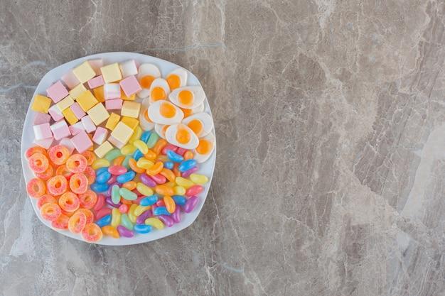 Verschiedene arten von bunten bonbons auf weißem teller.