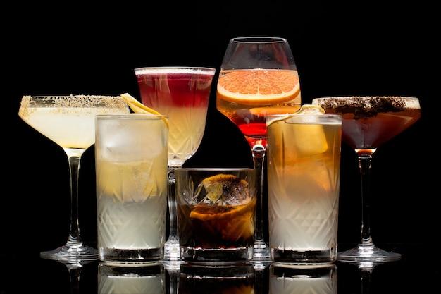 Verschiedene arten von cocktails sind auf einem schwarzen hintergrund isoliert.