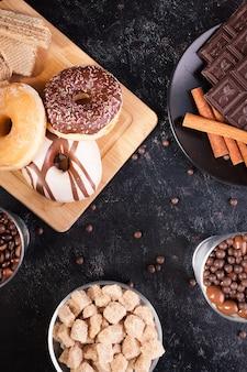 Verschiedene arten von desserts auf einem schwarzen holztisch im studiofoto
