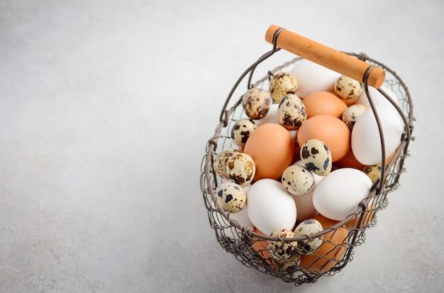 Verschiedene arten von eiern in einem korb auf einem grauen konkreten hintergrund.