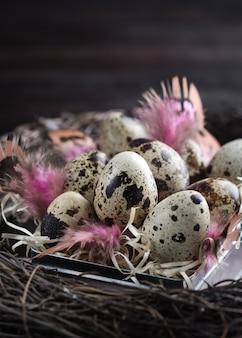 Verschiedene arten von eiern in einem nest mit federn auf einem hölzernen hintergrund. ostern-konzept