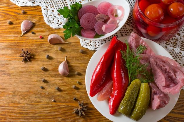 Verschiedene arten von eingelegtem gemüse. eingelegte gurken, tomaten, kohl, pfeffer, gemüse, zwiebeln und knoblauch werden auf einem tisch im alten stil mit handgefertigter tischdecke serviert. hausgemachtes fermentiertes gemüse