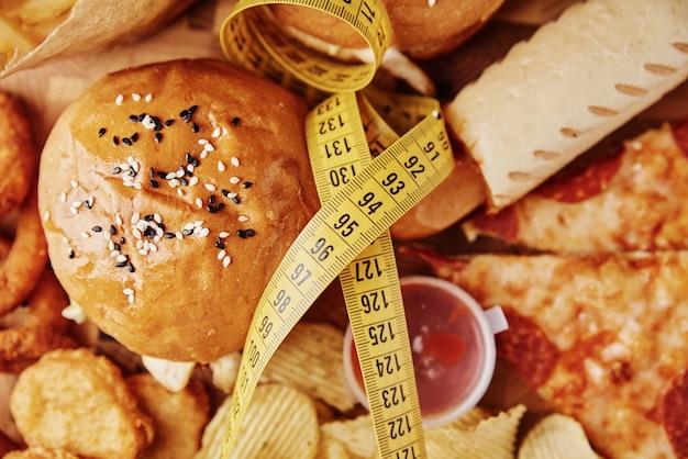 Verschiedene arten von fast food und snacks auf dem tisch mit maßband