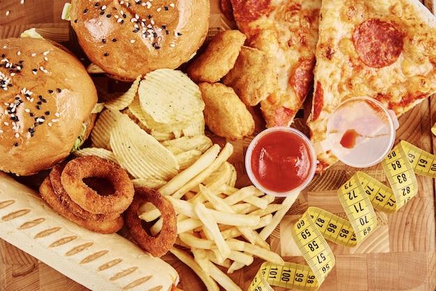 Verschiedene arten von fastfood und snacks auf dem tisch mit maßband
