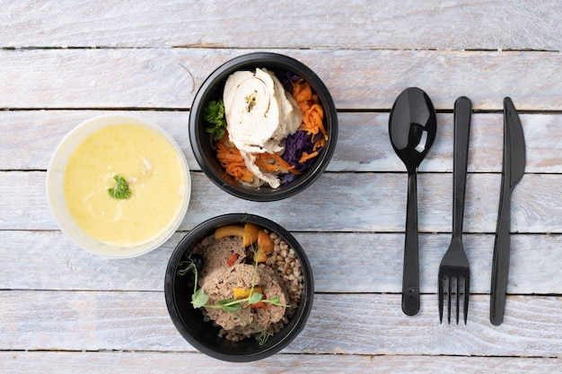 Verschiedene arten von fertiggerichten in folienbehältern auf dem holztisch, draufsicht. plastiklöffel, gabel und messer