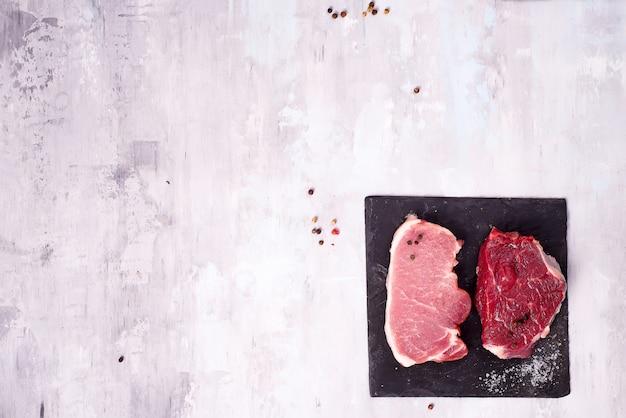 Verschiedene arten von fleisch auf dunklem schieferschneidebrett. schlanke proteine.