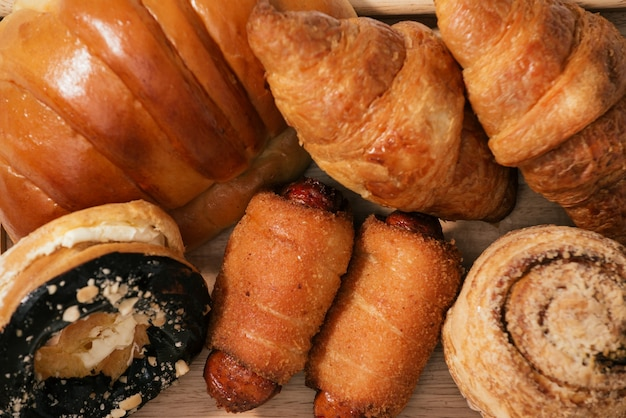 Verschiedene arten von frisch gebackenem brot, serviert auf holztablett