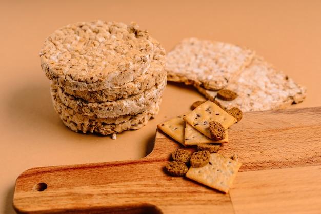 Verschiedene arten von gesunden vollkorn-knäckebroten und keksen auf brauner wand auf einem holzbrett