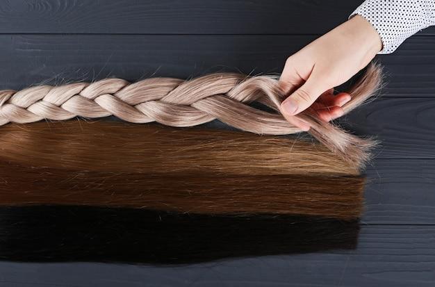 Verschiedene arten von haaren.blonde, rote und braunhaarige abschnitte.haarverlängerungskonzept.