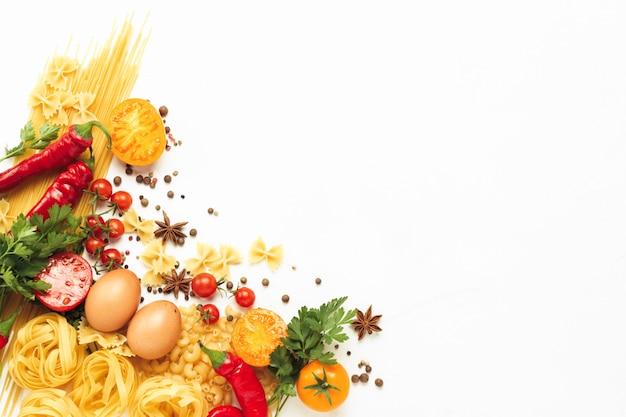 Verschiedene arten von italienischen nudeln, nestern, spaghetti, gewürzen, glühender chilipfeffer, hühnereier, tomaten, kirsche, hellweißer steinhintergrund. flache lage, draufsicht
